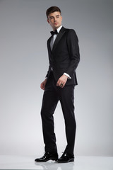 young man in tuxedo standing and looking down to side