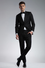 relaxed elegant young man standing with legs crossed