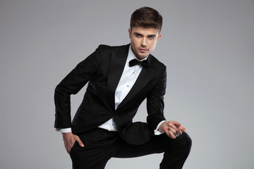 portrait of handsome man in tuxedo leaning on his leg
