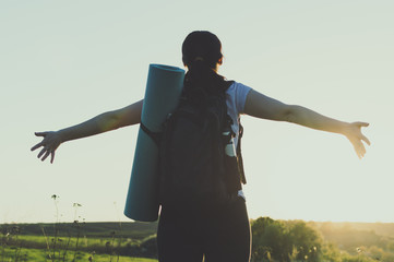 Young female backpacker standing with open arms opposite to the sunset. Concept of the vacation, travel, journey, success, freedom, backpacking, hiking.