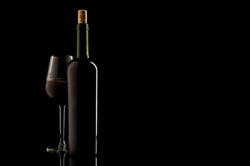Wine bottle with cork and glass on black isolated background
