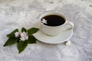 Cup of coffee serving with lilac and leaves