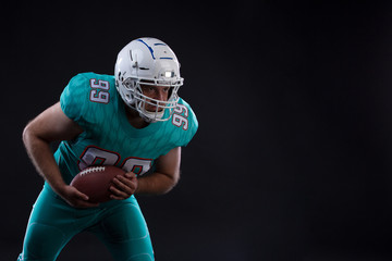 Portrait of American football player holding a ball in both his arms. Copy space. Rugby