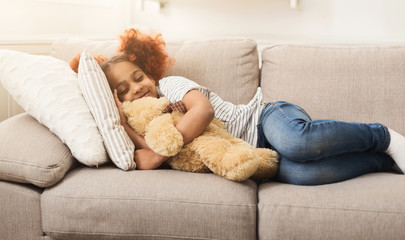 Little happy african-american girl sleeping on couch at home