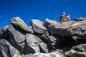 Hikers rest on the stone while hiking