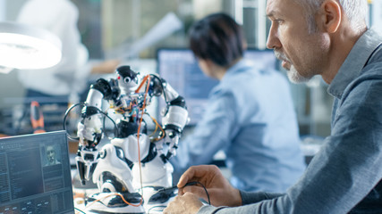 Senior Electronics Engineer Works With Robot, Programming it with Laptop. In the Background Laboratory with Technical Personnel Working.
