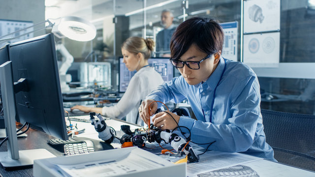 Electronics Engineer Works with Robot Checking Voltage and Program Response time. Computer Science Research Laboratory with Specialists Working.