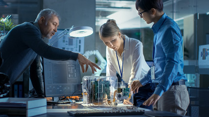 Team of Computer Engineers Lean on the Desk and Choose Printed Circuit Boards to Work with,...