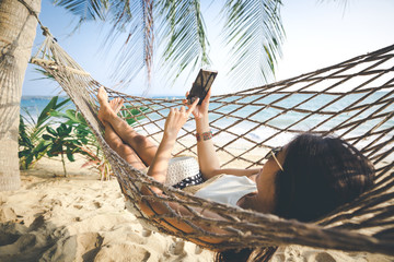 Happy woman using mobile phone in hammock Wall mural