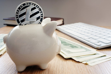 Savings in cryptocurrency. Litecoin and piggy bank.