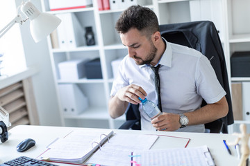 A man is sitting at a table in the office, working with documents and opening a bottle of water.