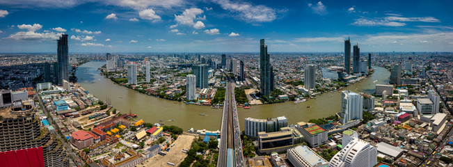 Fototapete - Aerial view of Bangkok skyline and skyscraper with BTS skytrain Bangkok downtown. Panorama of Sathorn and Silom business district Bangkok Thailand with blue sky and clouds.
