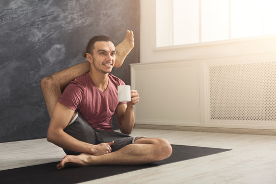 Young man in flexible yoga pose drinking tea