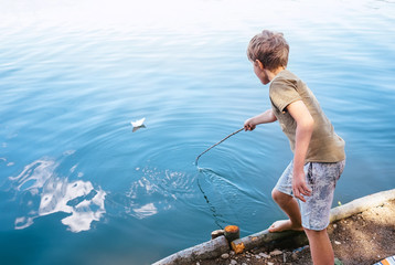 Boy plays with paper boat and launches it on the lake