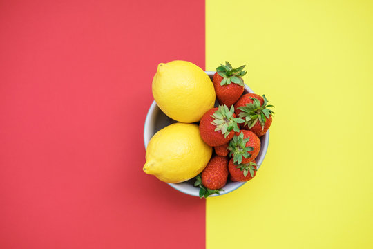 Fresh lemons and strawberries in a bowl on a yellow and red background. Flat lay, top view