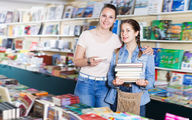 Young woman with girl in school age buying books