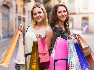 Two young women holding shopping bags.