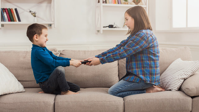 Siblings fighting over remote control at home