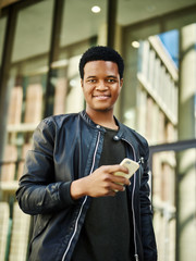 Portrait of handsome African American man in black leather jacket smiling at camera while walking down street with cell phone in his hand