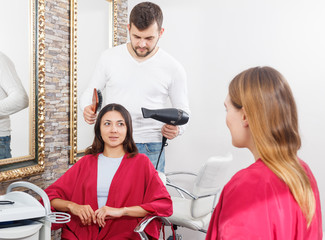 Professional hairdresser styling and drying hair with fen of woman
