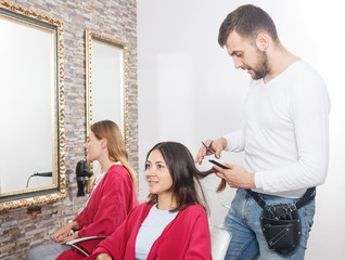 Young man professional hairdresser cut female's hair in salon