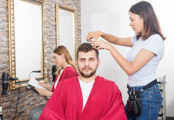 Woman professional hairdresser cut male's hair in hairdressing salon