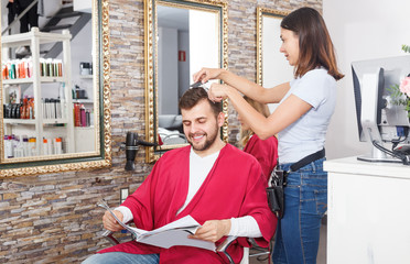 Young female hairdresser cuts hair of young man client  at salon
