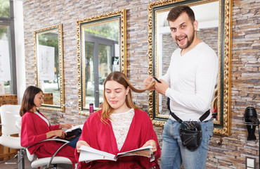 Adult hairdresser working with female client in hairdressing salon