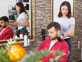 Girl hairdresser cuts hair of young man client  at beauty salon