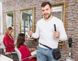 Male hairdresser  standing in beauty studio, clients on background