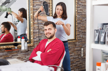 Girl professional hairdresser styling and drying hair with fen of man