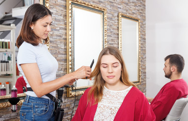 Young girl hairstylist working with  female's hair  in salon