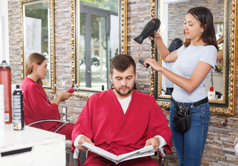 Young woman  hairstylist drying hair with blow dryer of guy