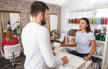 Young man client talking with woman assistant about  services