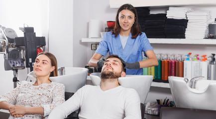 Adult girl hairdresser washing hair  of  positive man  in salon