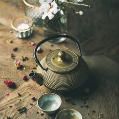 Traditional Asian tea ceremony arrangement. Golden iron teapot, cups, dried rose, candles and almond blossom flowers over vintage wooden table background, selective focus, square crop