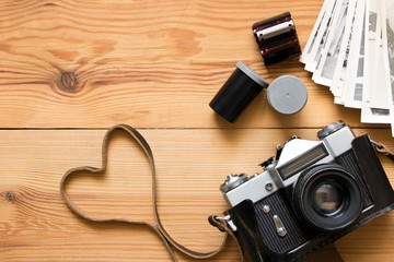 Old vintage camera, film and photos on wooden table