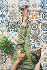 Lazy morning on terrace. Flat-lay of womans legs in cosy linen pants, plant, cat and cup of coffee in hand over colorful moroccan tile floor, top view
