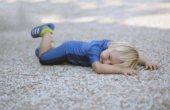 Bébé garçon en maillot de bain allongé sur les cailloux