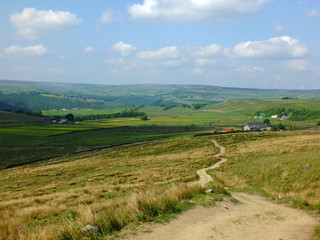 a long winding footpath running downhill in stoodley moor in yorkshire with fields and farms in the distance with the pennine hills on the horizon on a sunny summers day with blue sky and clouds