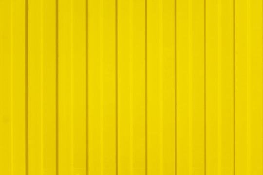 A corrugated fence of yellow metal sheets with screw. Texture of metal fence