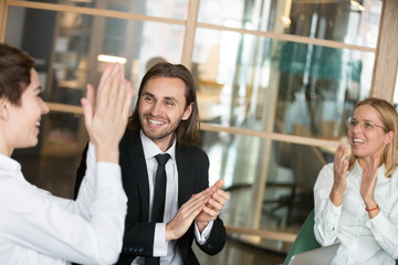 Crop of excited business partners laughing cheering congratulating colleague with successful startup project during company meeting, associates clapping greeting coworker, good deal, contract win