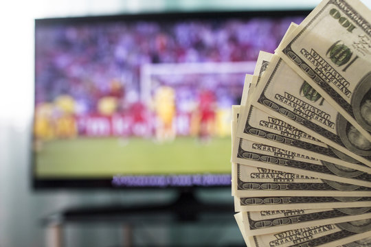 Dollars against the backdrop of a TV set for football, football and money