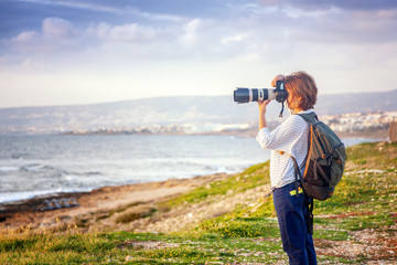Young girl professional photographer on the beach with a camera in hand, travel and remote work, blogger
