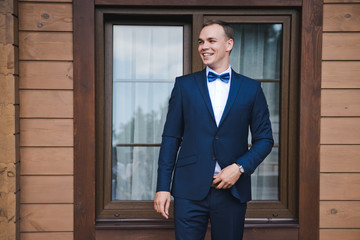 Morning of the groom. The groom smiles in a blue suit and a bow tie. Outdoor. A wooden brown house.