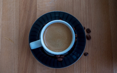 espresso cup with black plate and coffe beans from above