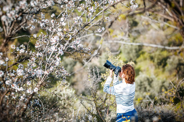 Young professional photographer woman takes a photo of nature while traveling