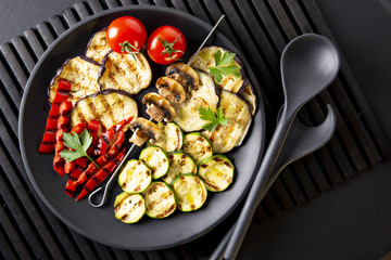 Grilled vegetables: eggplant, zucchini, pepper. Skewer with mushrooms. On a black plate and a black background. Toned.