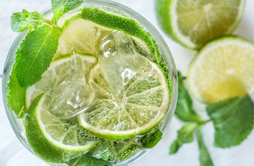 Fresh lemonade from lime or mojito with ice on a white wooden rustic background. Close-up. Top view