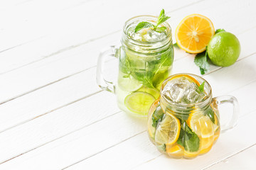Two glass glasses with homemade lemonade from lime and lemon, sliced citrus on a white wooden rustic background. Copy space